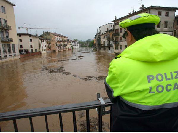 Un ufficiale di Polizia municipale di spalle sul ponte guarda preoccupato il fiume a pochi centimetri dal manto stradale. Anche per l'argine la sensazione è di stare a Venezia invece siamo a Vicenza