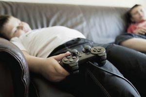 OBESITÀ-bambini-in-sovrappeso-giocano-su-divano