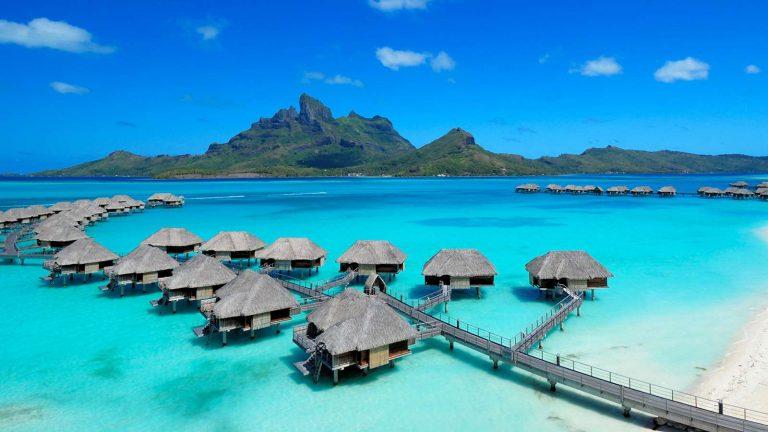 Le camere di un resort, all'interno dei caratteristici bungalow, circondate dal mare cristallino di Bora Bora