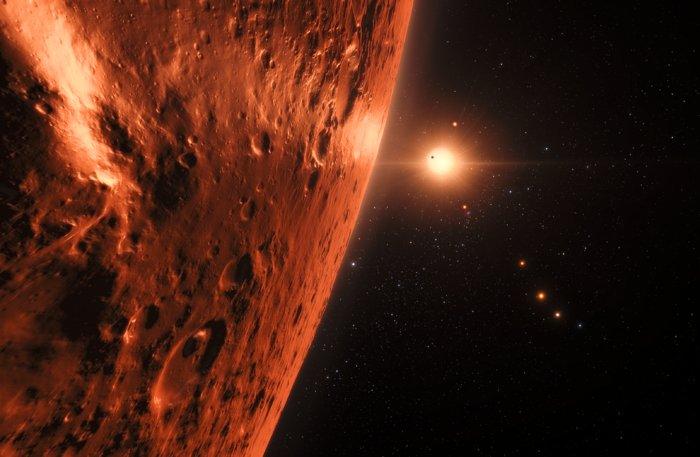 Questa rappresentazione artistica mostra la veduta appena sopra la superficie di uno dei pianeti del sistema di TRAPPIST-1. Almeno sette pianeti orbitano questa nana ultrafredda a circa 40 anni luce dalla Terra e sono tutti più o meno della stessa dimensione della Terra. Molti di questi si trovano alla giusta distanza dalla propria stella madre per avere acqua liquida sulla superficie. Credit: ESO/M. Kornmesser/spaceengine.org