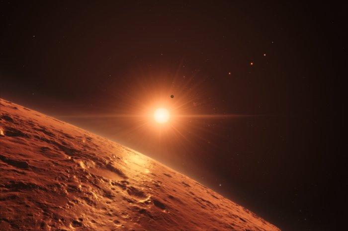 Questa rappresentazione artistica mostra la veduta dall'alto dalla superficie di uno dei pianeti centrali del sistema di TRAPPIST-1, con il bagliore della stella che illumina la superficie rocciosa. Sono almeno sette i pianeti in orbita intorno alla stella nana ultrafredda a circa 40 anni luce dalla Terra e hanno tutti una dimensione simile a quella della Terra. Molti sono alla giusta distanza dalla stella perché l'acqua possa essere liquida sulla superficie. Credit: ESO/M. Kornmesser/spaceengine.org