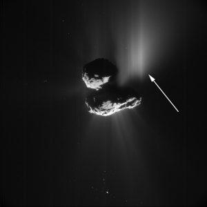 Immagine della NavCam di Rosetta presa il 10 luglio 2015 a 156,58 chilometri di distanza dal nucleo della cometa 67P. La risoluzione dell'immagine è di 15,81 metri per pixel. La freccia bianca mostra l'outburst prodotto dal collasso del crinale Aswan (in ombra in questa ripresa). Crediti: ESA/Rosetta/NavCam – CC BY-SA IGO 3.0
