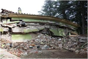 Amatrice: edificio collassato per il peso di coperture e solai in calcestruzzo armato e gravanti su murature fragili e vulnerabili, non progettate per sostenerli (Foto QUEST).