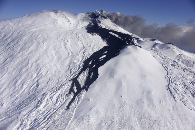 Figura 2 - Versante meridionale dell'Etna. In primo piano, in nero, si staglia nettamente sul bianco della neve la colata lavica il cui fronte si attesta a sud ovest di Monte Frumento Supino (MFS) a quota 2450 m s.l.m. In secondo piano il Cratere di Sud Est (CSE) che emette cenere in direzione est e a sinistra il cratere Bocca Nuova (BN). Fotografia di M. Cantarero, INGV.