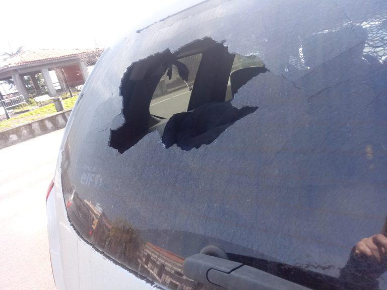 Il parabrezza posteriore di un'auto distrutto da una bomba vulcanica a Milo